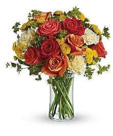 Dark orange, orange and coral roses are gathered with light yellow carnations, yellow button mums and fresh green bupleurum and pittosporum in a simple glass gathering vase