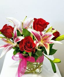 Beautiful red roses and lilies overflowing in a cube and accented with ribbon