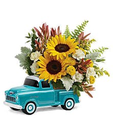 Our chevy truck is overflowing with sunflowers, spray roses and carnations, mums and accented with greens.
