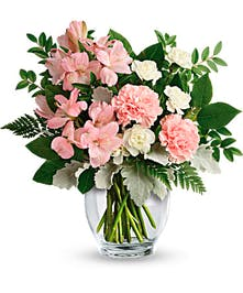 This delicate arrangement includes pink alstroemeria, pink carnations, white miniature carnations, dusty miller, huckleberry, leatherleaf fern, and lemon leaf.
